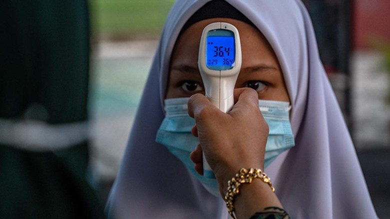 A high school teacher checks the temperature of a student on the first day after being reopened following restrictions to halt the spread of the COVID-19 coronavirus in Kuala Lumpur on June 24, 2020. (Photo by Mohd RASFAN / AFP)