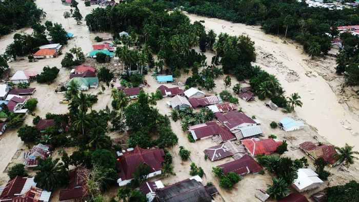 Foto udara kondisi perkampungan tertimbun lumpur akibat terjangan banjir bandang di Desa Radda, Kabupaten Luwu Utara, Sulawesi Selatan, Rabu (15/7/2020). Banjir bandang yang terjadi akibat tingginya curah hujan yang membuat sungai Salukula dan Meli meluap tersebut mengakibatkan 21 orang meninggal dunia dan puluhan warga dilaporkan masih dalam pencarian, sementara  ratusan rumah rusak berat dan hilang tertimbun material lumpur. ANTARA FOTO/Moullies/ABHE/foc.