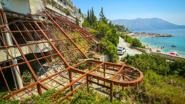 Kupari, Croatia- July 19, 2017 : The iron construction of an old ruined hotel Goricina in abandoned Yugoslavian military resort with a view of the beach on the Adriatic sea in Kupari, Croatia.