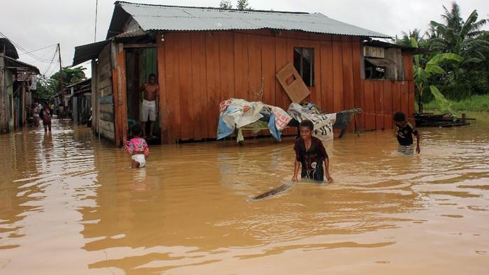 Anak-anak bermain air saat banjir menggenangi Kelurahan Klasabi, Kota Sorong, Papua Barat, Jumat (17/7/2020). Sejumlah wilayah Kota Sorong mengalami banjir dan longsor akibat hujan dengan intensitas tinggi sejak Kamis (16/7/2020). Data sementara dari Badan Penanggulangan Bencana Daerah (BPBD) menyebutkan tiga orang meninggal  tertimbun longsor dan seorang meninggal karena sengatan listrik. ANTARA FOTO/Olha Mulalinda/pras.
