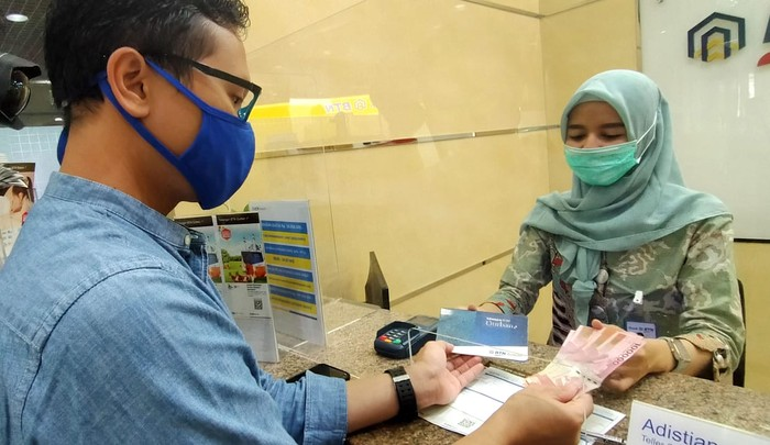 "Teller BTN Syariah sedang melayani nasabah menabung ke rekening tabungan BTN Qurban di Kantor Cabang Syariah BTN di Jakarta, Jumat (17/7). Menyambut hari raya Idul Adha, BTN Syariah mengenalkan  Tabungan  BTN Qurban ib yaitu produk tabungan untuk merencanakan pembelian dan penyaluran hewan qurban dengan bagi hasil yang menguntungkan dan kompetitif berdasarkan prinsip syariah dengan akad ""Mudharabah Mutlaqah"" (Investasi). Adapun program ini menjadi salah satu strategi BTN syariah menggenjot DPK, per Juni 2020 DPK BTN syariah menembus Rp 20,8triliun atau sudah 90 persen mencapai target tahun 2020."