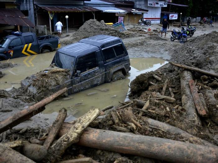 Kondisi rumah dan mobil yang tertimbun lumpur akibat terjangan banjir bandang di Kecamatan Masammba, Kabupaten Luwu Utara, Sulawesi Selatan, Rabu (15/7/2020). Banjir bandang yang terjadi akibat tingginya curah hujan tersebut mengakibatkan 16 orang meninggal dunia dan puluhan warga dilaporkan masih dalam pencarian, sementara ratusan rumah rusak berat dan hilang.ANTARA FOTO/Abriawan Abhe/aww.