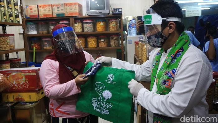 Wakil Gubernur DKI Jakarta Ahmad Riza Patria (tengah) memberikan kantong belanja ramah lingkungan kepada pedagang di Pasar Tebet Barat, Jakarta, Jumat (17/7/2020). Kegiatan tersebut dalam rangka kampanye penggunaan kantong belanja ramah lingkungan guna meminimalisir pemakaian kantong plastik.