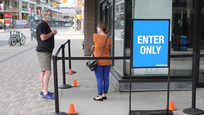 A sporting goods store clerk (L) explains shopping rule to a customer May 19, 2020 in Ottawa, Canada. - Ontario, Canadas most populous province, is allowing stores with street access to reopen, along with hospital surgery rooms, dog parks and golf courses. (Photo by Dave Chan / AFP)