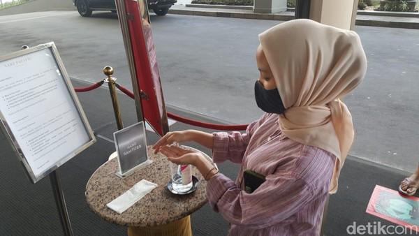 Setelah pemeriksaan suhu tubuh, kamu juga harus membersihkan tangan dengan hand sanitizer yang tersedia di bagian pemeriksaan. Terlihat petugas keamanan dan para staff hotel mengenakan masker dan face shield. (Syanti/detikcom)