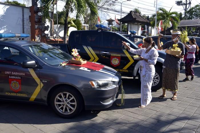 Pemuka agama Hindu dan petugas kepolisian mengupacarai persenjataan saat rangkaian persembahyangan Hari Raya Tumpek Landep di Polsek Denpasar Selatan, Bali, Sabtu (18/7/2020). Hari Tumpek Landep dirayakan umat Hindu untuk melakukan pembersihan dan penyucian dengan makna memohon penajaman pikiran dalam menggunakan ilmu pengetahuan serta teknologi yang disimboliskan dengan mengupacarai persenjataan atau peralatan berbahan besi yang sifatnya tajam. ANTARA FOTO/Fikri Yusuf/hp.