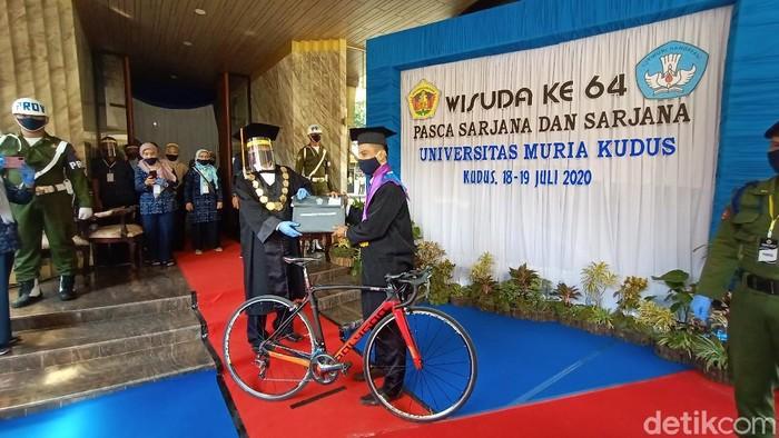 Universitas Muria Kudus (UMK) menggelar wisuda secara drive-thru. Bedanya ada wisudawan yang mengendarai sepeda saat prosesi sakral tersebut.