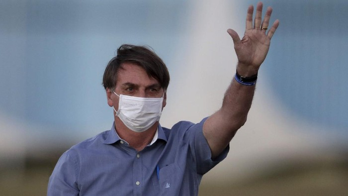 Brazils President Jair Bolsonaro who is infected with COVID-19, wears a protective face mask as he waves to supporters during a Brazilian flag retreat ceremony outside his official residence Alvorada Palace, in Brasilia, Brazil, Friday, July 17, 2020. On Thursday evening, the federal health ministry reported that the country had passed 2 million confirmed cases of virus infections and 76,000 deaths. (AP Photo/Eraldo Peres)