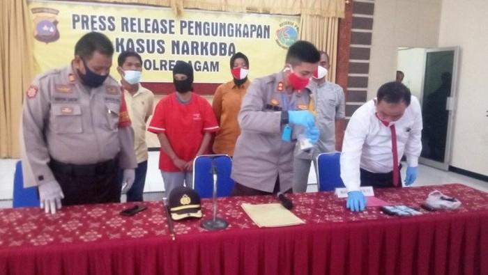 Kapolres Agam AKBP Dwi Nur Setiawan sedang melihatkan barang bukti di Aula Wibisono Polres Agam, Senin (20/7). (ANTARA/Yusrizal)
