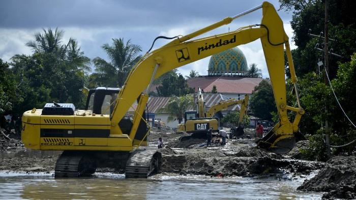 Sejumlah alat berat mengeruk material lumpur yang menutup jalan trans Sulawesi di Kabupaten Luwu Utara, Sulawesi Selatan, Senin (20/7/2020). Sejumlah jalan termasuk jalan trans Sulawesi terus dilakukan pengerukan lumpur akibat banjir bandang untuk memperlancar jalur transportasi. ANTARA FOTO/Abriawan Abhe/wsj.