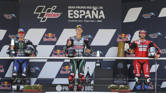 Race winner Fabio Quartararo of France, center, celebrates at the podium with Maverick Vinales of Spain, left, and Andrea Dovizioso of Italy at the end of the Spanish Motorcycle Grand Prix at the Angel Nieto racetrack in Jerez de la Frontera, Spain, Sunday, July 19, 2020. (AP Photo/David Clares)