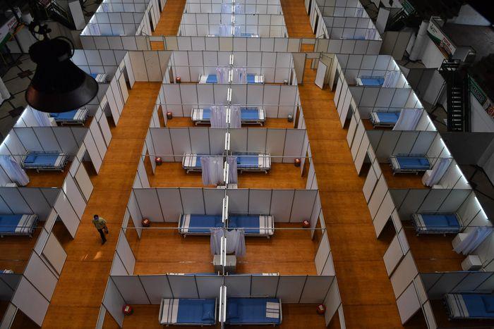 Pekerja merapikan tempat tidur di Sarana Olaraga Tri Dharma yang dijadikan ruang isolasi mandiri COVID-19 di Gresik, Jawa Timur, Senin (20/7/2020). Petrokimia Gresik mengubah sarana olaraga tersebut menjadi ruang isolasi mandiri COVID-19 yang terdiri dari 40 ruangan dengan kapasitas 80 tempat tidur yang telah dilengkapi sejumlah fasilitas pendukung, hal itu bertujuan sebagai bentuk antisipasi tingginya kasus mewabahnya virus Corona di Surabaya Raya. ANTARA FOTO/Zabur Karuru