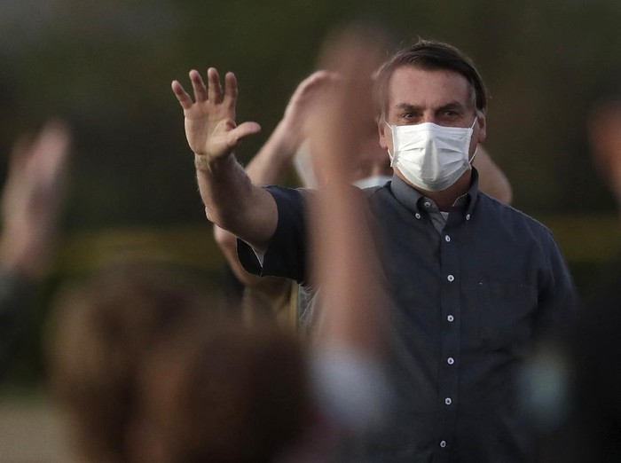 Brazils President Jair Bolsonaro who is infected with COVID-19, wears a protective face mask as he waves to supporters during a Brazilian flag retreat ceremony outside his official residence the Alvorada Palace, in Brasilia, Brazil, Monday, July 20, 2020. (AP Photo/Eraldo Peres)