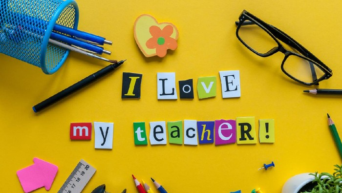 i love my Teacher - text made with carved letters on yellow desk with office or school supplies on pupil table.