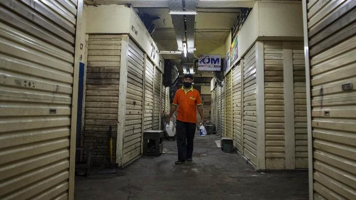Petugas keamanan berjalan di depan toko yang tutup di Pasar Asem Reges, Jakarta Barat, Selasa (21/7/2020). Pengelola Pasar Asem Reges menutup sementara pasar tersebut dari Senin (20/7) hingga Rabu (22/7) menyusul satu orang pedagang terkonfirmasi positif COVID-19 berdasarkan hasil tes usap (swab test).