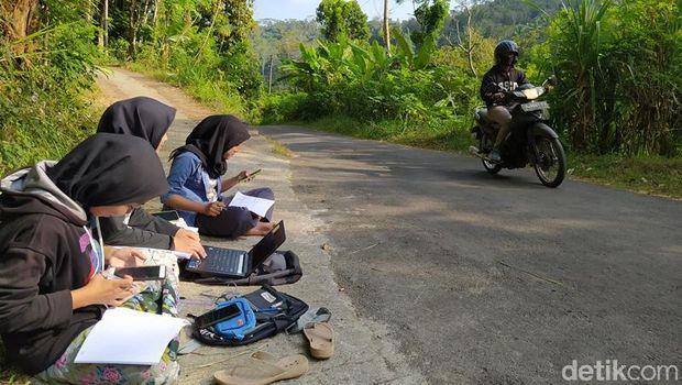 Teara (tengah), mahasiswi yang mengerjakan tugas daring di pinggir jalan di Magelang, Selasa (21/7/2020).