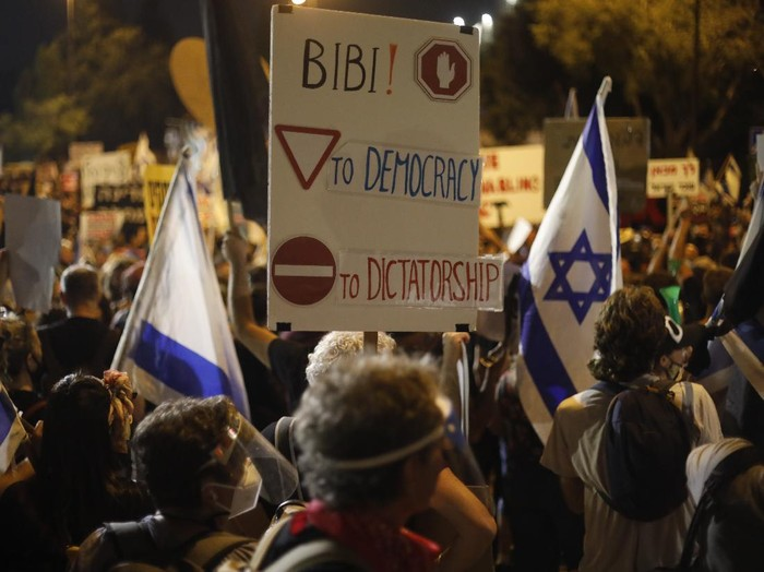 Demonstrators hold signs during a protest against Israels Prime Minister Benjamin Netanyahu in front of the Knesset, Israels parliament in Jerusalem, Tuesday, July 21, 2020. Thousands of Israelis marched back to Netanyahus official residence after protesting outside the Knesset, the countrys parliament. (AP Photo/Ariel Schalit)