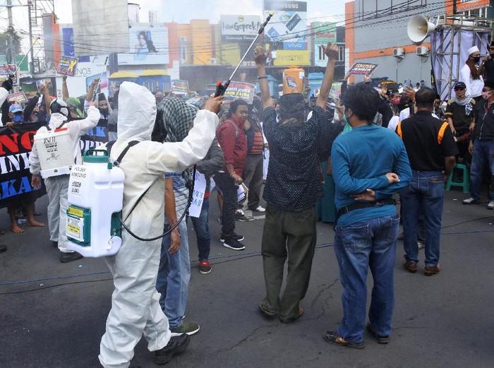 Sejumlah warga gelar aksi unjuk rasa di bundaran DPRD Jember, Jatim. Di tengah aksi, sejumlah petugas semprotkan cairan disinfektan kepada para demonstran.