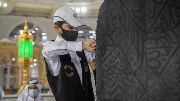 Setiap tahun, para penjaga pintu kakbah mendapat tugas untuk mengangkat kain hitam ini saat menjelang pelaksanaan ibadah haji. (Reasah Alharamain/Twitter)