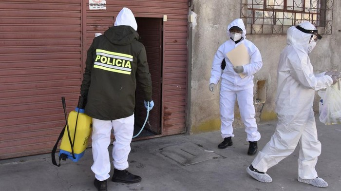 Health workers and police officers in protective suits carry out an epidemiological evaluation at the houses of police officers to detect possible infections of the novel coronavirus, COVID-19, in El Alto, Bolivia, on July 18, 2020. - The pandemic has killed at least 596,742 people worldwide since it surfaced in China late last year and more than 14 million have been infected, according to an AFP tally at 1100 GMT on Saturday based on official sources. (Photo by Aizar RALDES / AFP)
