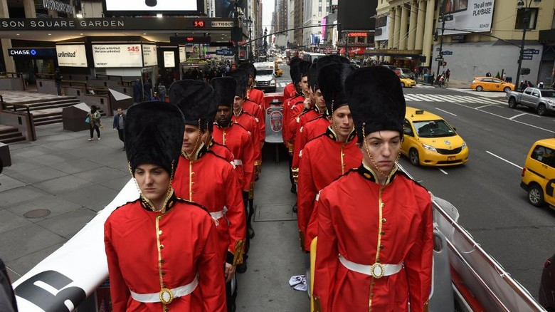 People dressed as Beefeaters pose on top of a tour bus in front of Madison Square Garden in New York on April 25, 2017, to promote the Paul McCartneys latest concert tour,