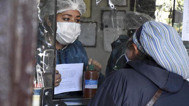 Warga membeli botol klorin dioksida di apotek di Cochabamba, Bolivia, Jumat, 17 Juli 2020. Warga rela mengntre  setiap pagi di Cochabamba untuk membeli botol kecil klorin dioksida, zat pemutih yang dianggap sebagai obat untuk COVID-19 dan berbagai penyakit lainnya. (Foto AP / Dico Solis)