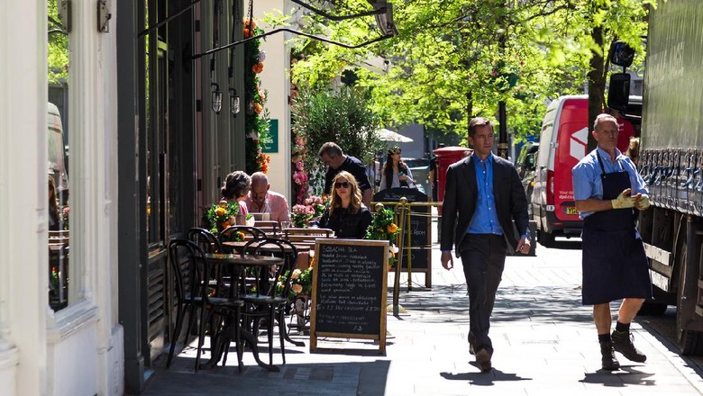 London, UK - 21 May, 2019: color image depicting people sitting at tables, eating and drinking outside a posh cake shop/cafe in the Belgravia area of London, UK. The exterior of the shop is decorated with beautiful garlands of fresh flowers. It is a beautiful day with bright blue sky. Room for copy space.
