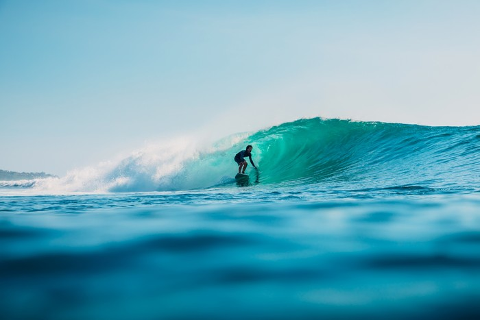 January 16, 2020. Bali, Indonesia. Surfer ride on ocean wave. Professional surfing in ocean at waves