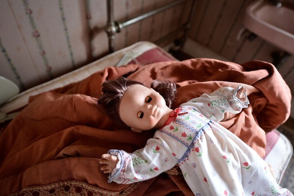 Kertas dinding dari tahun 1920-an masih melekat di sana. Pun dengan berbagai barang-barang seperti kasur dan boneka-boneka yang terbaring di atas bantal.(Foto: Getty Images/Bethany Clarke)
