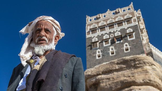portrait of old senior man with the typical yemenite dress, The turban, the neck scarf and Jambiya in Sanaa, Yemen. Jambiya is a traditional dagger and a mandatory attribute of Yemeni men's suit. The rocky palace on the back ground in Dar al-Hajar town.