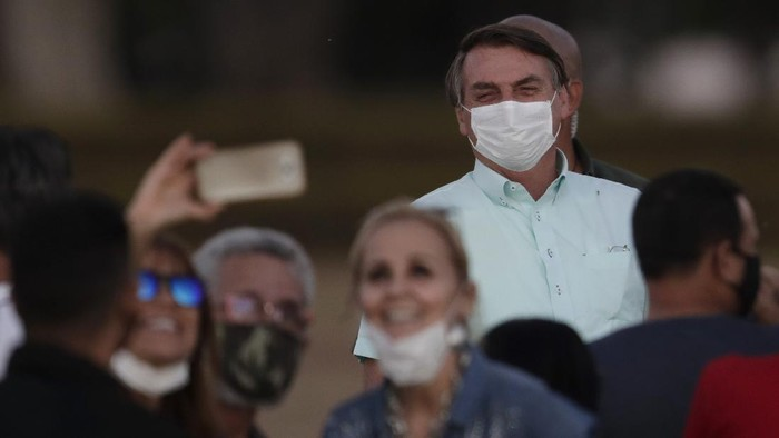 Supporters pose for a selfie as Brazils President Jair Bolsonaro, who is infected with COVID-19, wears a protective face mask while attending a Brazilian flag retreat ceremony outside his official residence the Alvorada Palace, in Brasilia, Brazil, Wednesday, July 22, 2020. Bolsonaro has tested positive for the new coronavirus for the third time, following his July 7 announcement that he had COVID-19, the Brazilian government confirmed. (AP Photo/Eraldo Peres)