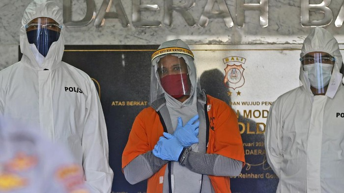 U.S. national Marcus Beam, center, wearing protective equipment as precaution against the coronavirus, is flanked by police as he is presented to the media during a press conference at the Regional Police Headquarters in Denpasar, Bali, Indonesia, Friday, July 24, 2020. Authorities on the resort island arrested Beam, an American fugitive accused of investment fraud in the United States involving hundreds of thousands of dollars, police said Friday. The U.S. Securities and Exchange Commission said on its website that Beam, of Woodridge, Illinois, is accused of misappropriating about $500,000 from investors that was supposed to be placed in investment funds. (AP Photo/Firdia Lisnawati)