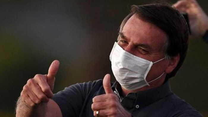 (FILES) In this file picture taken on July 20, 2020 Brazilian President Jair Bolsonaro gives the thumbs up to supporters from the Alvorada Palace in Brasilia, amid the new coronavirus pandemic. - Brazilian President Jair Bolsonaro announced on July 25, 2020 he has tested negative for the new coronavirus more than two weeks after being diagnosed on July 7, attributing his recovery to an unproven malaria drug. (Photo by EVARISTO SA / AFP)