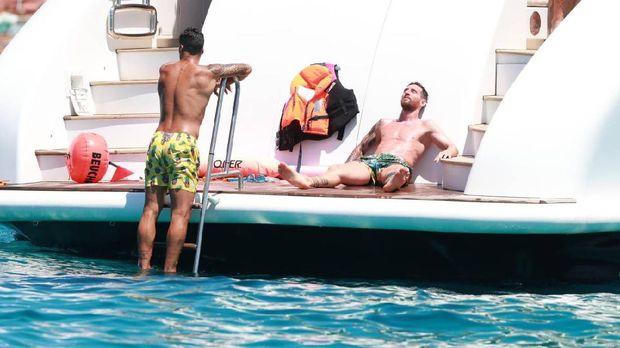 Lionel Messi dan Luis Suarez liburan bareng di atas kapal pesiar di Pulau Ibiza, Spanyol.