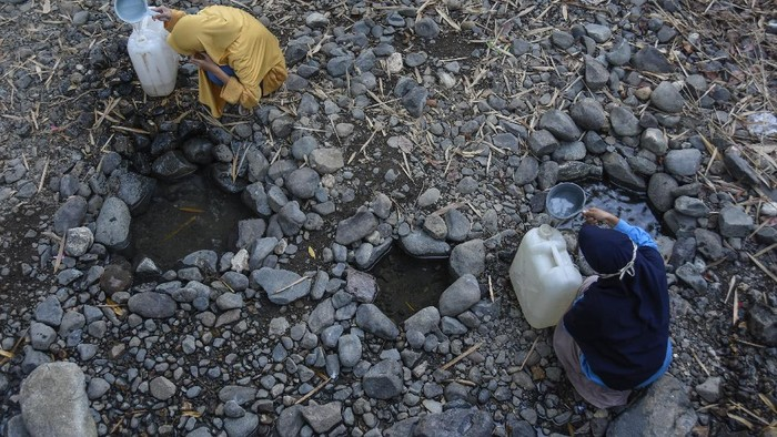 Sejumlah perempuan berjalan membawa jerigen untuk mengambil air di sungai yang airnya mulai menyusut di Desa Kelawis, Kecamatan Orong Telu, Kabupaten Sumbawa, NTB, Sabtu (25/7/2020). Warga di daerah tersebut sejak dua bulan lalu mengalami kesulitan mendapatkan air bersih untuk kebutuhan mencuci dan mandi akibat semakin menyusutnya debit air sungai yang melintas di Desa Kelawis dampak musim kemarau. ANTARA FOTO/Ahmad Subaidi/foc.