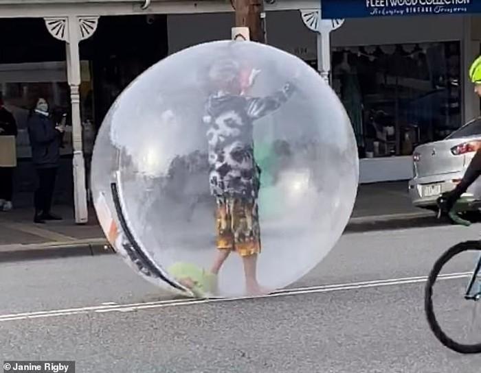Pria berjalan menggunakan bola plastik raksasa.