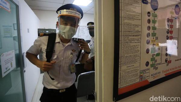 Dengan berseragam lengkap serta memakai masker dan face shield, seorang masinis bergegas menuju kereta untuk mengoperasikan kereta sesuai tujuan.