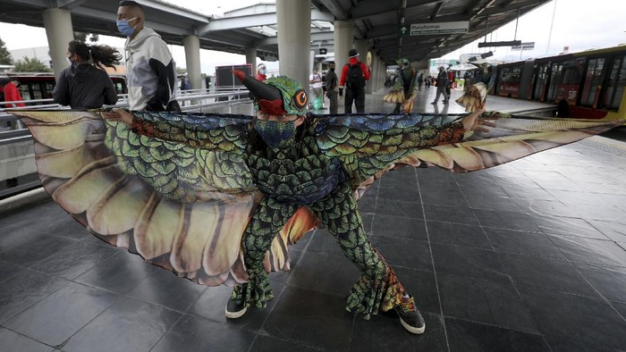 Musicians from Bogota's Youth Philharmonic Orchestra and dancers in hummingbird costumes perform for commuters at a bus stop in Bogota, Colombia, Friday, July 24, 2020. They offered a one-hour concert that they say they hope will serve as a