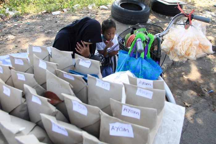 Pelajar kelas VIII MTs Darul Ulum, Sovi Dwi Aprilia (kiri) bersama adiknya, Tri Wahyu, yang masih kelas I SD belajar sambil berjualan nasi bungkus di pinggir jalan kawasan Delta Sari, Waru, Sidoarjo, Jawa Timur, Selasa (28/7/2020). Sovi berjualan nasi untuk membantu orangtuanya sekaligus mencari tambahan untuk membeli paket data internet agar bisa belajar secara daring. ANTARA FOTO/Umarul Faruq/foc.