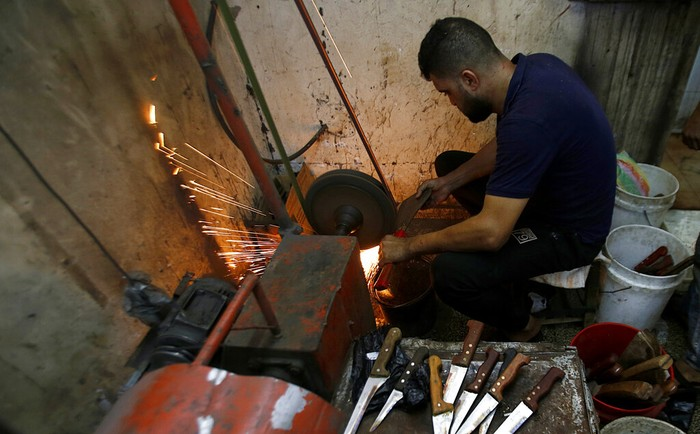 A Palestinian man sharpens a knife that will be used to slaughter cattle or cut meats during the Muslim festival of sacrifice Eid al-Adha, in a workshop in Gaza City, Tuesday, July 28, 2020. Eid al-Adha, or Feast of Sacrifice, Islam's most important holiday marks the willingness of the Prophet Ibrahim to sacrifice his son. (AP Photo/Hatem Moussa)