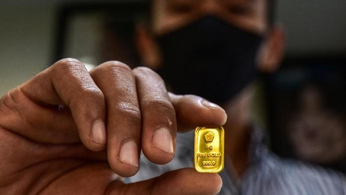 Seorang pegawai menunjukkan kepingan emas di toko dan perhiasan di Kota Pekanbaru, Riau, Selasa (28/7/2020). Harga emas batangan PT Aneka Tambang (Antam) pada 28 Juli 2020 menembus Rp1 juta/gram yang merupakan posisi tertinggi sepanjang masa emas Antam diperjualbelikan. ANTARA FOTO/FB Anggoro/foc.