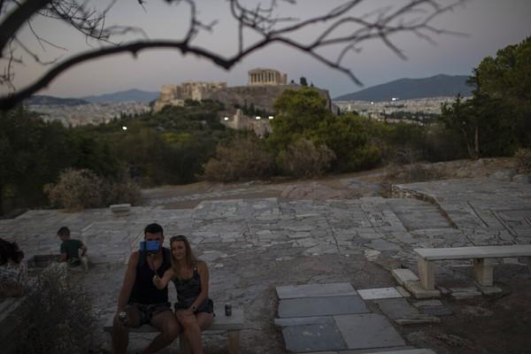 Sepasang kekasih mengabadikan diri mereka dengan ponsel di atas bukit Areopagus.