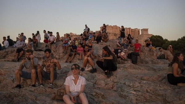 Para wisatawan menikmati waktu sore mereka dengan duduk santai dan melihat pemandangan.