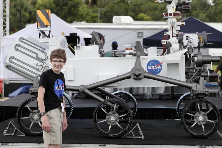 Alexander Mather, of Burke, Va. stands next to a model of the Mars 2020 rover he named in a contest during a news conference at the Kennedy Space Center Tuesday, July 28, 2020, in Cape Canaveral, Fla. Mather, submitted the winning entry in NASAs