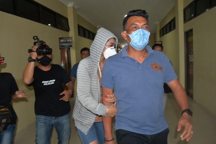 Personel kepolisian membawa artis berinisial VS (tengah) saat akan menjalani pemeriksaan di Polresta Bandar Lampung, Lampung, Rabu (29/7/2020). Vernita Syabilla (VS) yang juga selebgram dan artis Film Televisi (FTV) tersebut ditangkap Polresta Bandar Lampung dari sebuah hotel berbintang di Bandar Lampung karena diduga terlibat dalam kasus prostitusi. ANTARA FOTO/ Ardiansyah/aww.