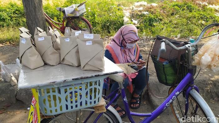 Kakak beradik di Sidoarjo belajar daring sambil berjualan nasi bungkus. Mereka yakni Sovi Dwi Aprilia dan Tri Wahyu.