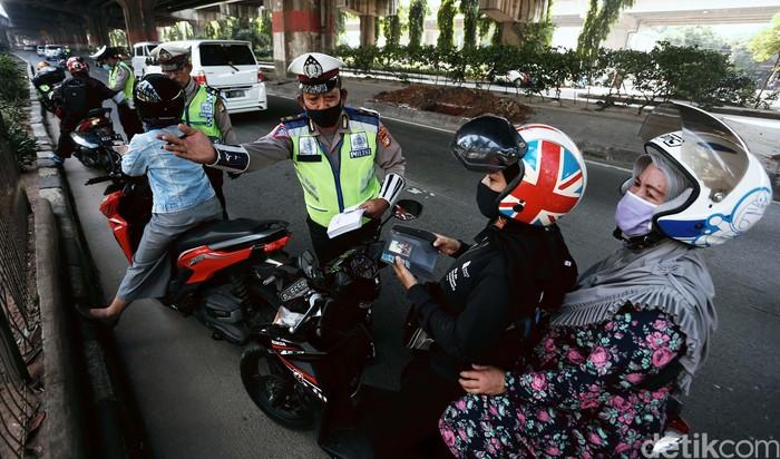 Polisi menggelar Operasi Patuh Jaya 2020, di Jalan DI Pandjaitan, By Pass, Jakarta Timur.  Mereka menindak pemotor yang memasuki jalur cepat.