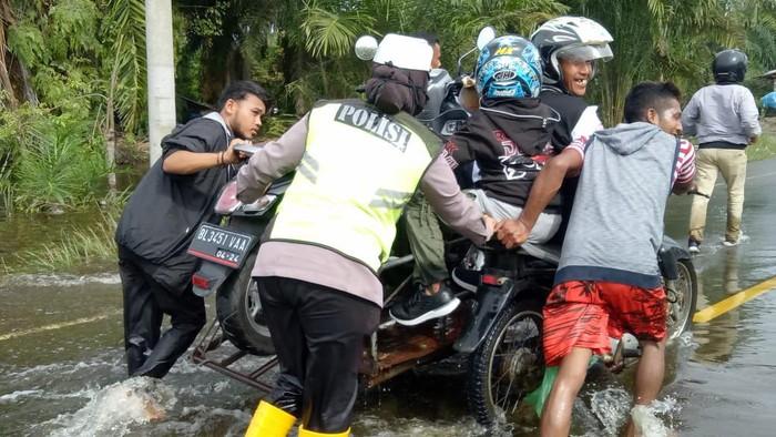 Sepeda motor diangkut becak karena banjir di Aceh Jaya.