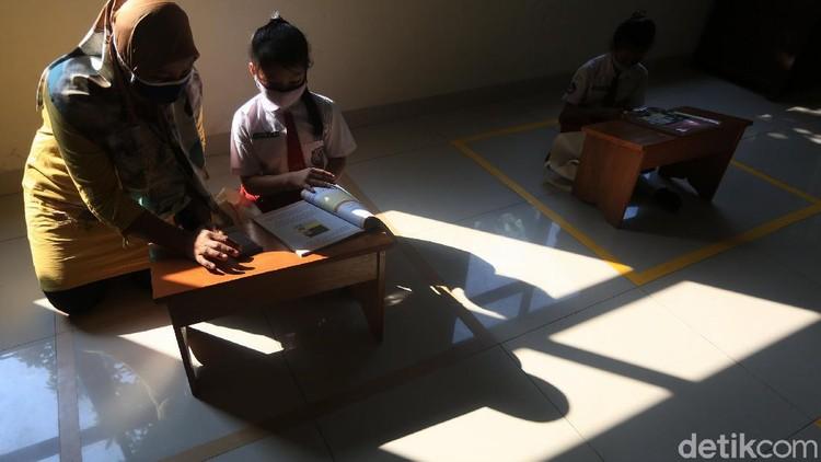 Anak-anak belajar di Aula Kelurahan Jati Rahayu, Kota Bekasi, Jawa Barat, Rabu (29/7/2020). Pihak kelurahan menyediakan fasilitas ruang belajar ber-AC dan wifi gratis bagi siswa. Tujuannya untuk membantu siswa yang selama ini sulit memenuhi paket kuota internet untuk belajar sekolah.