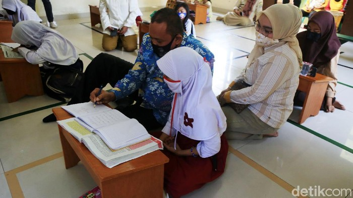 Wakil Wali Kota Bekasi Tri Adhianto mengajari siswi yang belajar di Aula Kelurahan Jati Rahayu, Kota Bekasi, Jawa Barat, Rabu (29/7/2020). Siswa-Siswi yang memiliki kendala dalam memperoleh kuota internet mereka belajar dengan mendapatkan wifi gratis yang disediakan oleh pihak kelurahan.